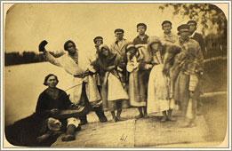 Группа хантов – участников «медвежьего праздника», который устраивался по поводу удачной охоты на медведя. Слева сидит музыкант с традиционным инструментом тор-сапль-юх («журавлиная шея деревянная»), под аккомпанемент которого во время праздника исполнялись обрядовые песни, пляски и танцы-пантомимы в честь добытого на охоте медведя, считавшегося «священным зверем». Фотография входит в состав большой коллекции, подаренной музею талантливым зоологом, антропологом и этнографом, хранителем Зоологического музея при Академии наук Иваном Семеновичем Поляковым (1847-1887). Она была сделана во время его экспедиции в Западную Сибирь в бассейн реки Обь в 1876 г.